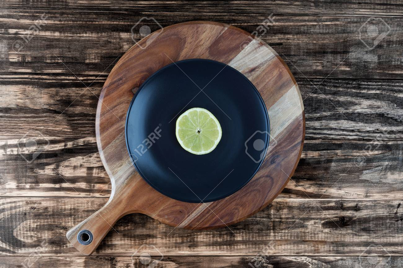 Slice Of Lemon On Black Plate And Round Chopping Board Looks Stock Photo Picture And Royalty Free Image Image 79518844