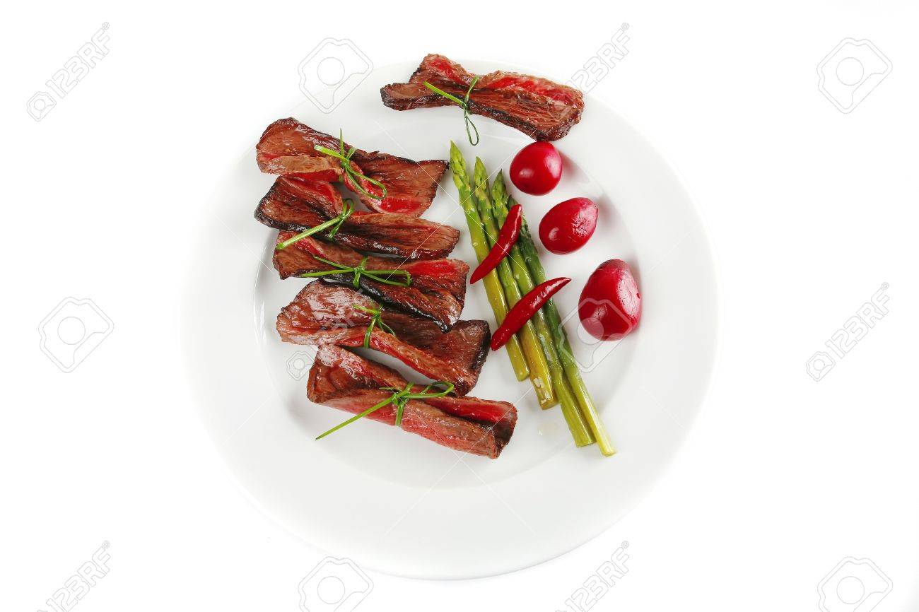 curved meat slices on white dish with vegetables Stock Photo - 7592012