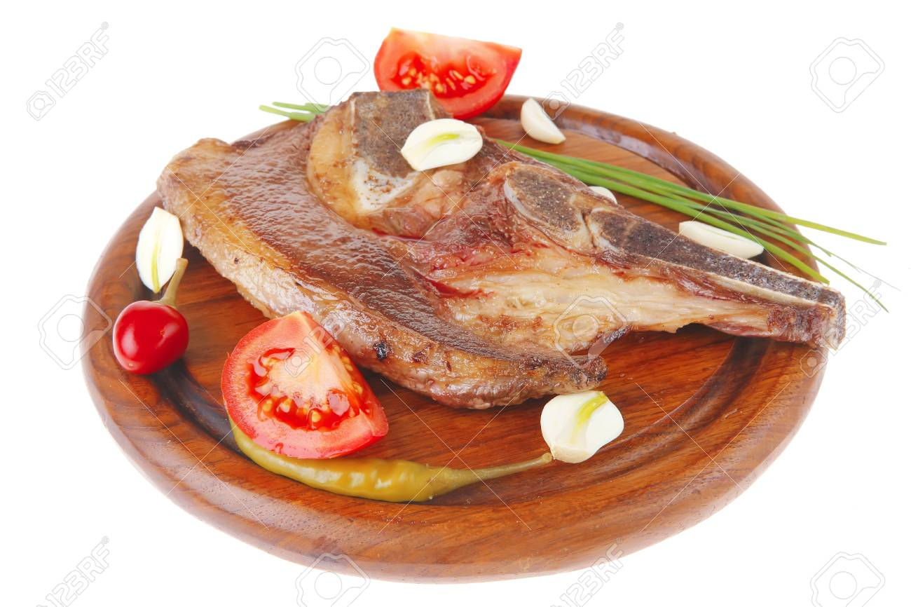 fresh hot roasted beef meat bone steak on red wooden plate with red hot pepper and capers isolated over white background Stock Photo - 9671045