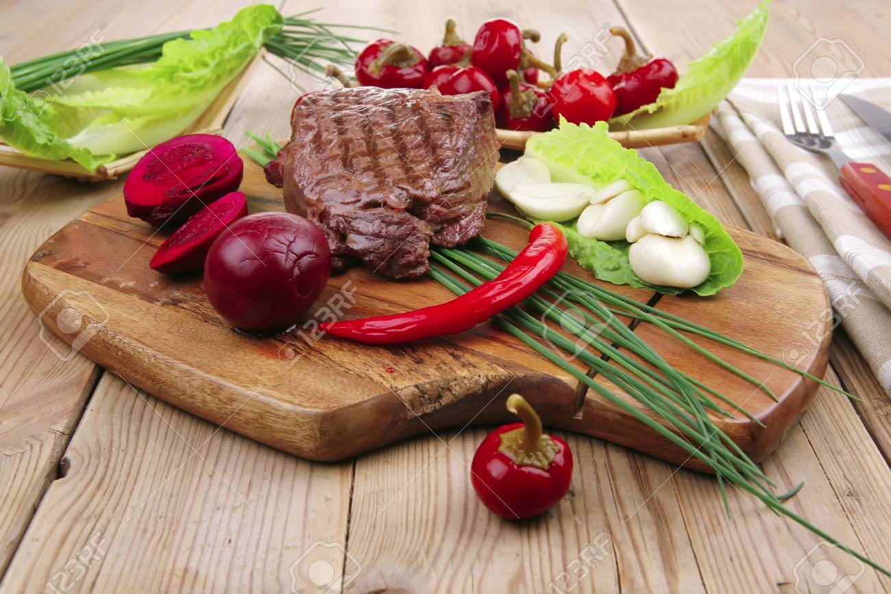 barbecued meat : beef ( lamb ) garnished with green lettuce and red chili hot pepper on wooden table with cutlery Stock Photo - 10389221