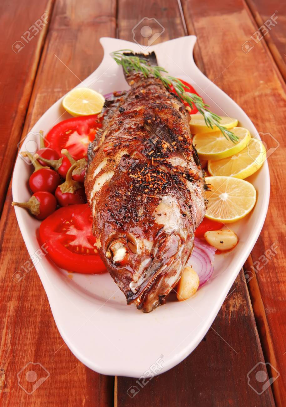 savory: whole fryed sunfish over wood with tomatoes lemons and peppers Stock Photo - 10620436