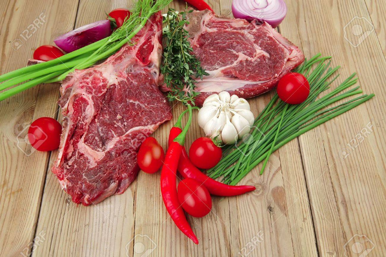 raw meat : boned fresh lamb ribs served with thyme , red chili pepper , cherry tomato , and green onion over wooden table Stock Photo - 10737993