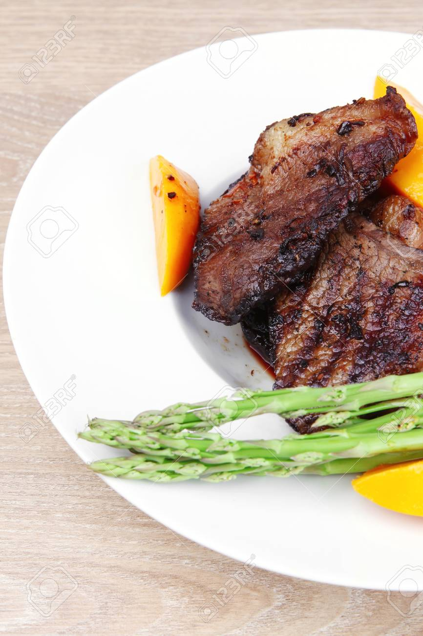 meat food : rare medium roast beef fillet with mango tomatoes and asparagus , served on white dish over wooden table Stock Photo - 11902855