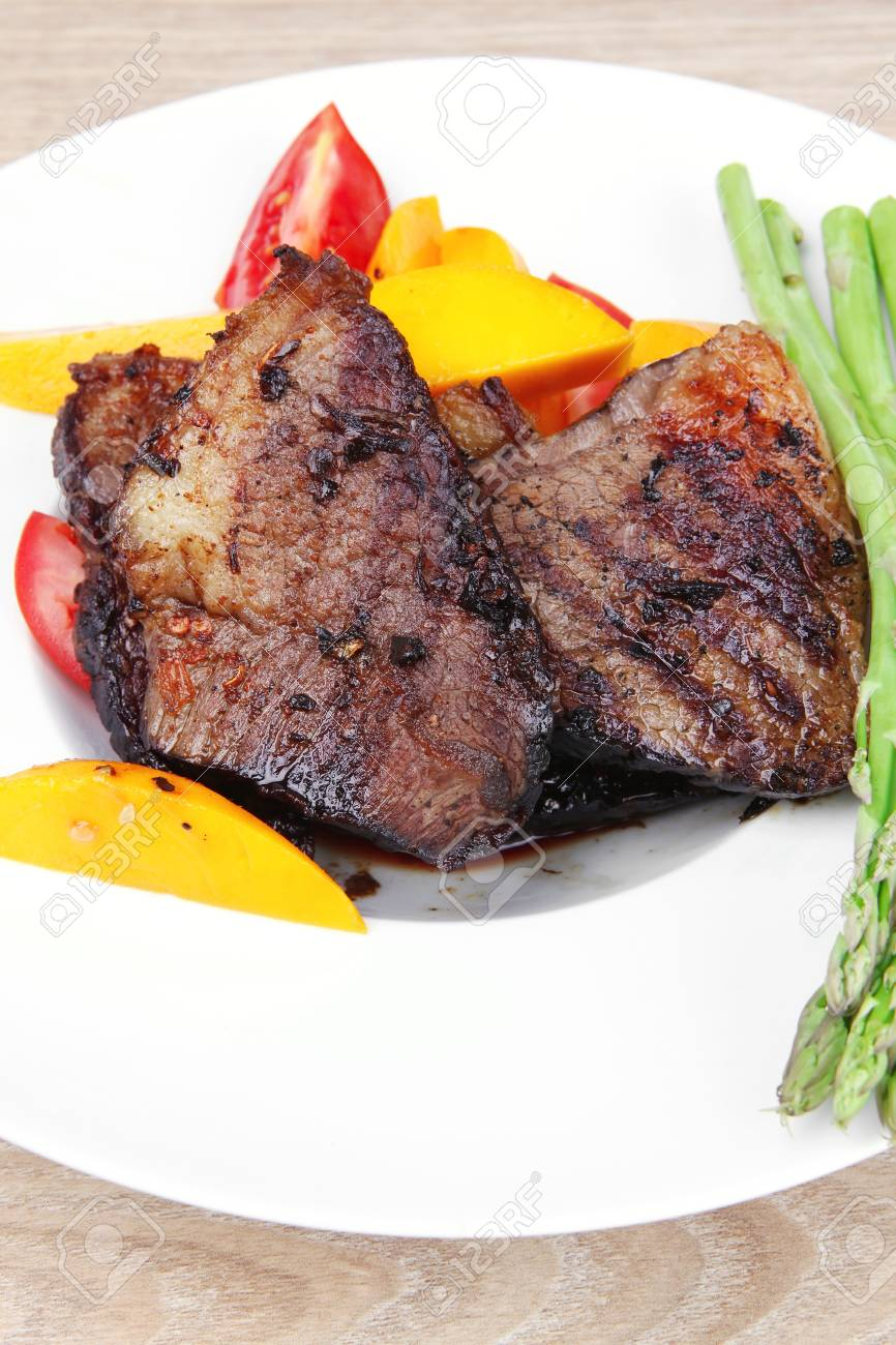 meat food : grilled red beef fillet with mango tomatoes and asparagus , served on white dish over wooden table Stock Photo - 12766679