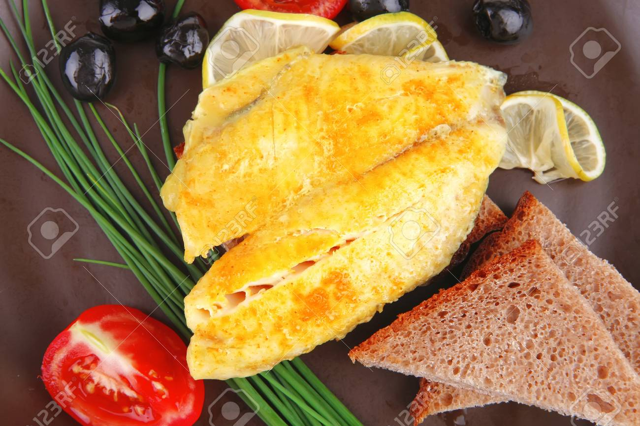 roast fish fillet with tomatoes,chives and bread on plate Stock Photo - 13809253