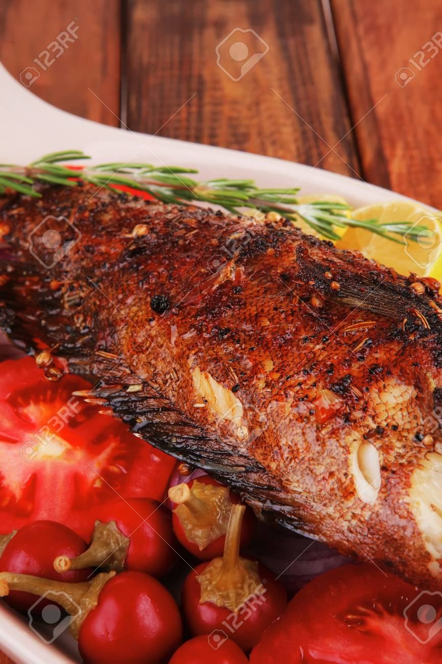 main course: whole fried seabass served on wood with lemons,tomatoes and peppers Stock Photo - 14945540