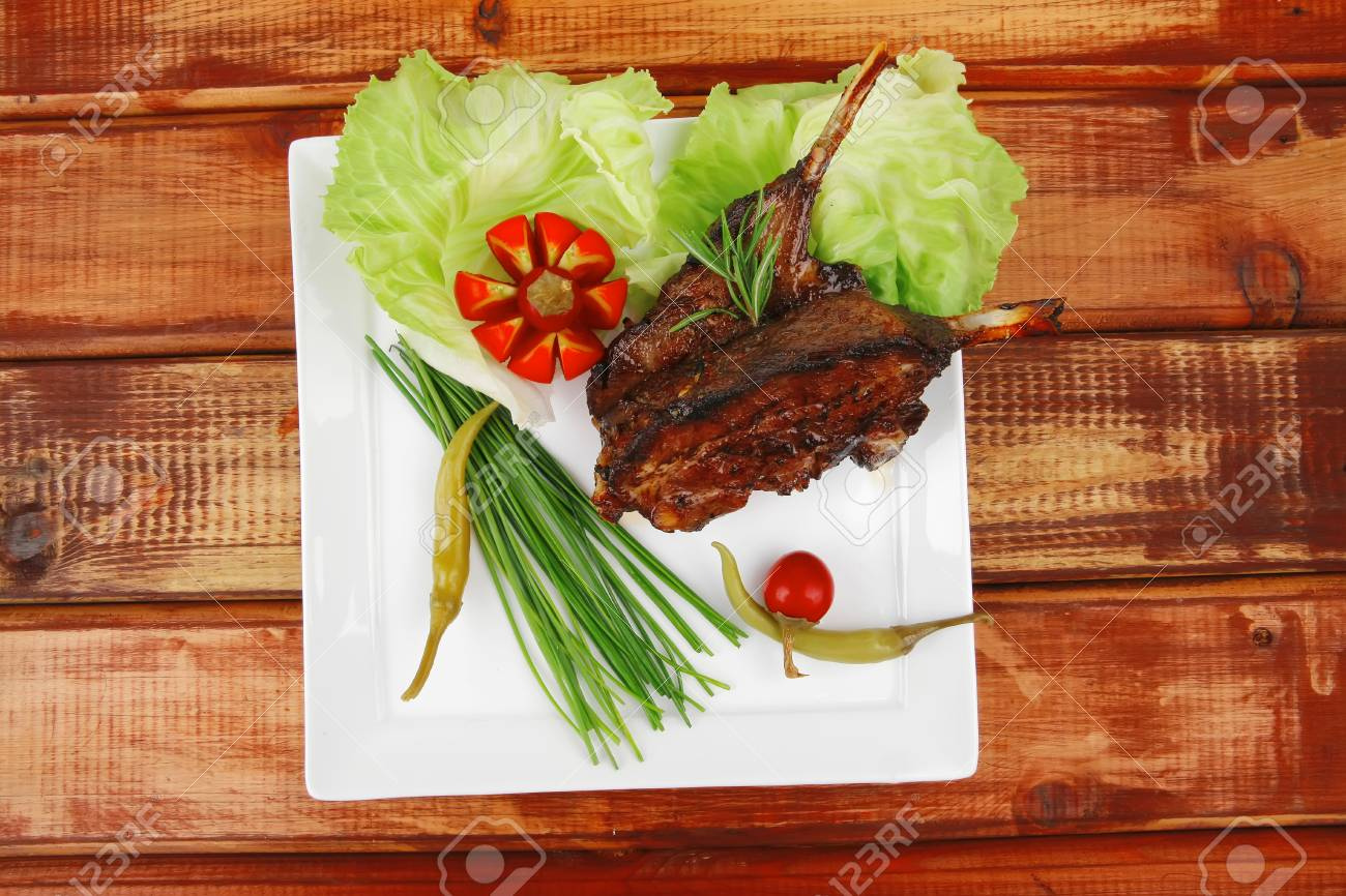 savory plate over wooden table: grilled ribs on white plate with chives, red hot peppers lettuce Stock Photo - 15729392
