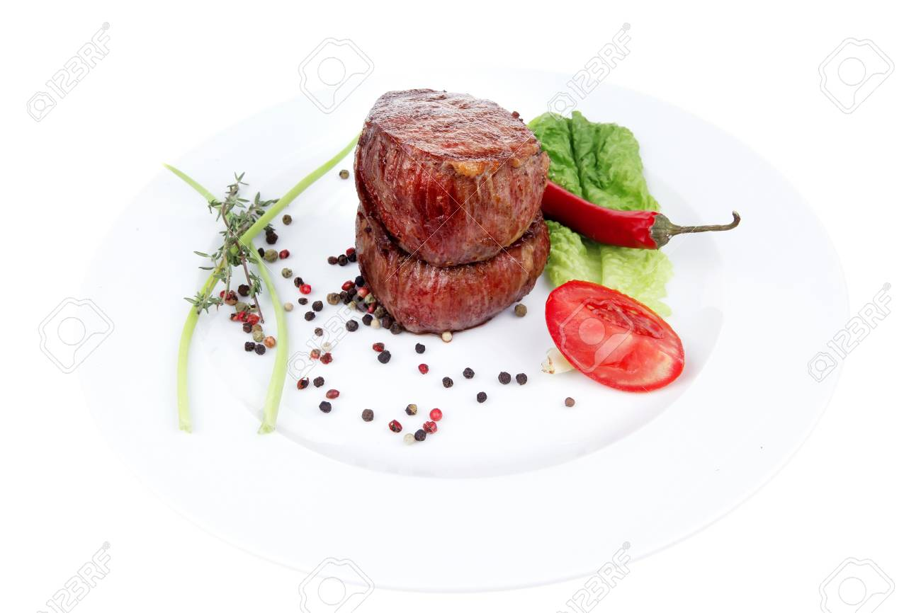 grilled beef fillet medallions on noodles with red hot chili pepper and salad leaf on white plate isolated over white background Stock Photo - 16027425