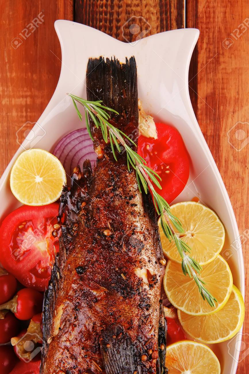 main course: whole fryed sunfish on wooden table with lemons and peppers Stock Photo - 16018515