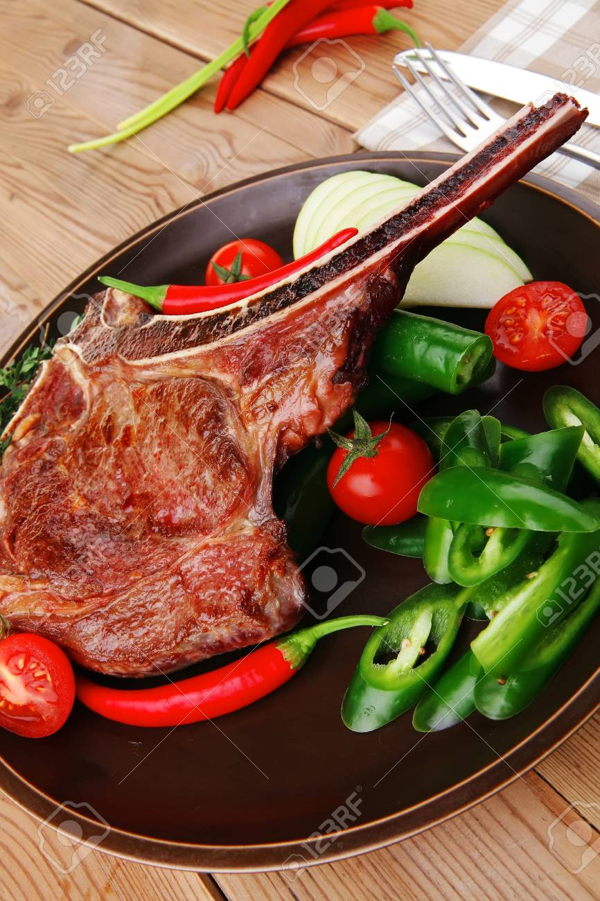 meat food : grilled beef spare rib on dark dish with thyme pepper and tomato on wooden table Stock Photo - 16149964