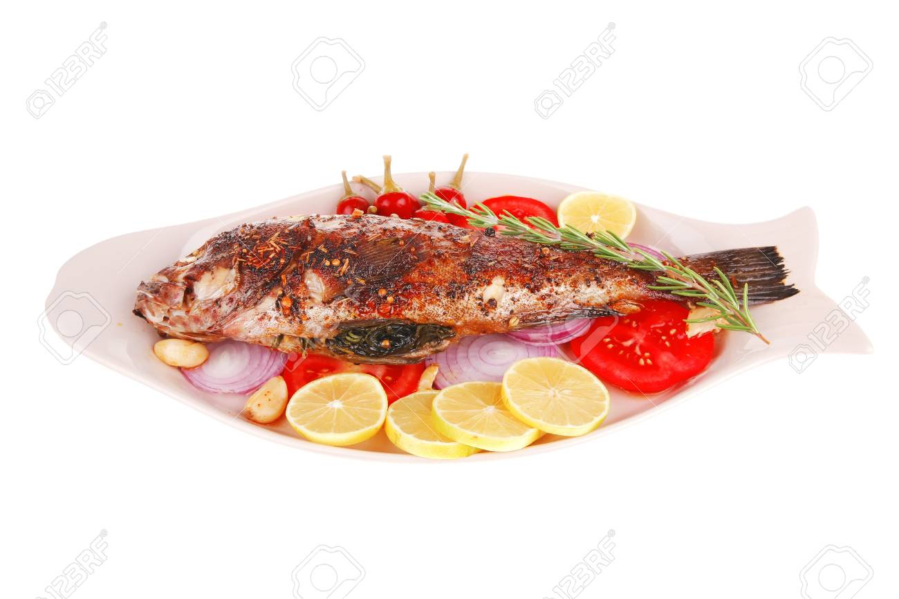 main course: whole fryed sunfish on plate with lemons and peppers Stock Photo - 16989599