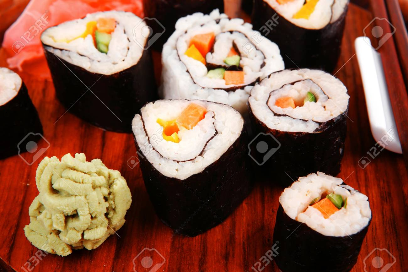 Japanese Traditional Cuisine - California Roll with Salmon (sake), Cream Cheese and Tuna (maguro) . on wooden plate with wasabi and ginger isolated over white background Stock Photo - 18801661