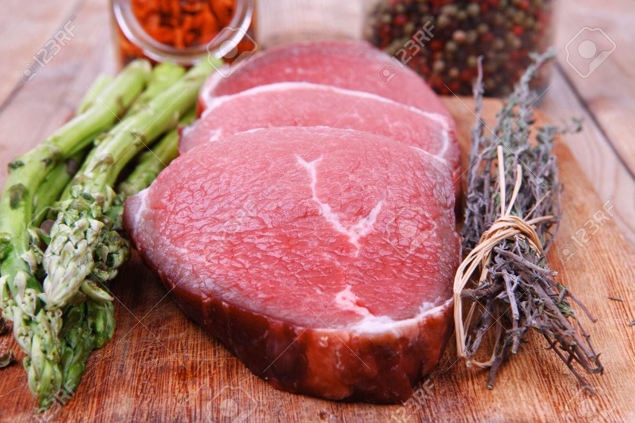 meat food : raw beef fillet on cutting board with asparagus and