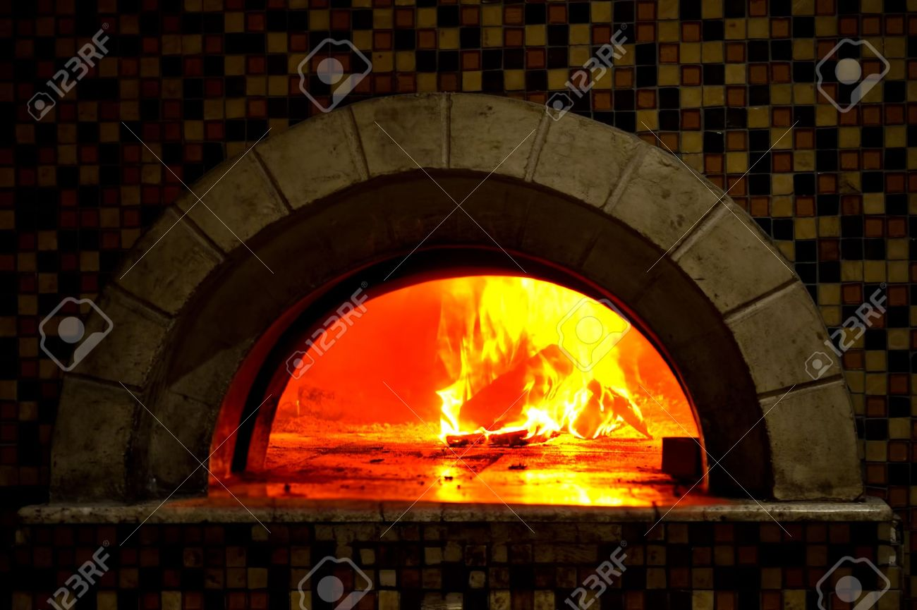 image detail of a wood fired pizza oven with fire blazing stock photo