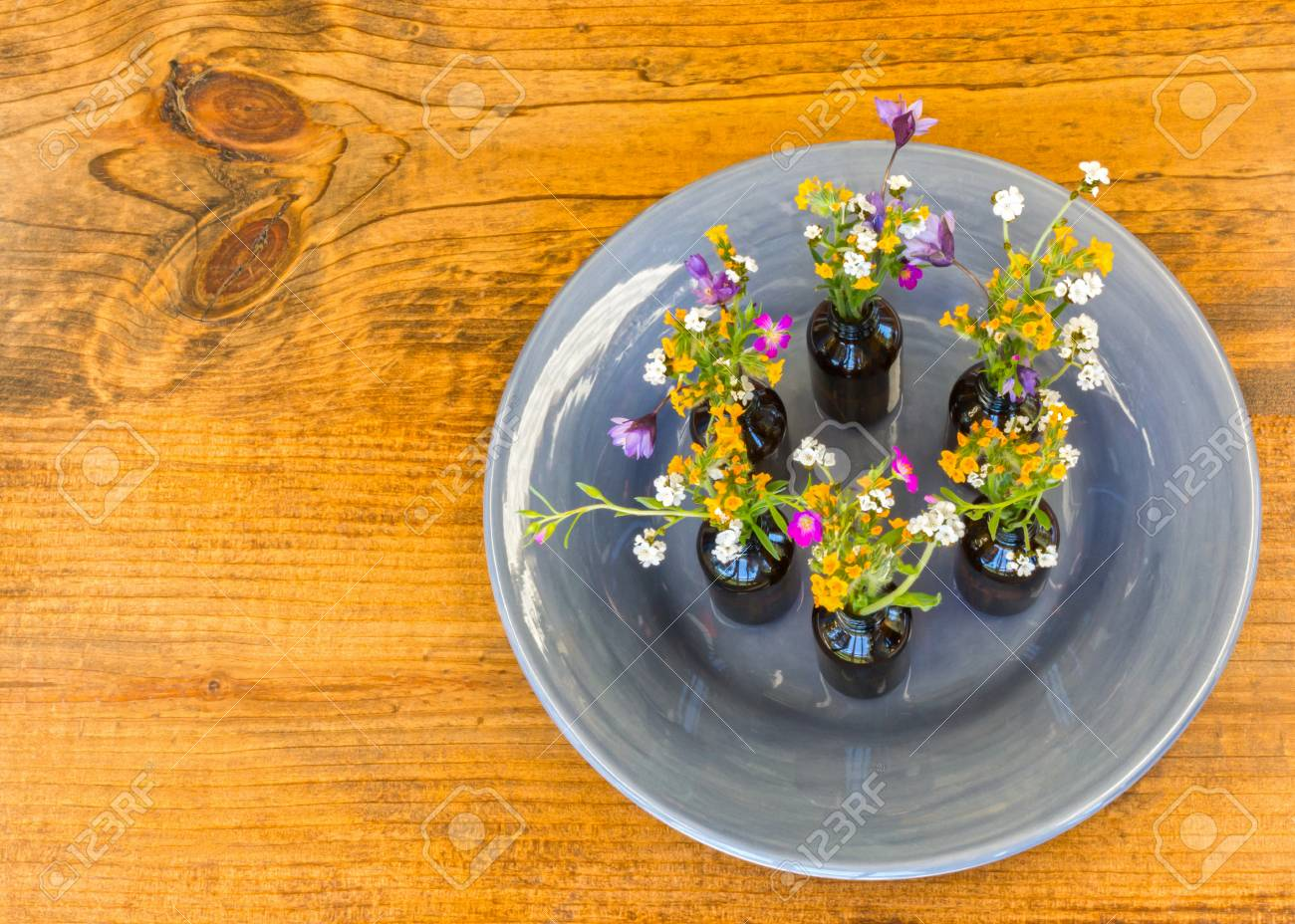 123RF.com & Gray Plate With Small Vases With Flowers Sitting on Wooden Table