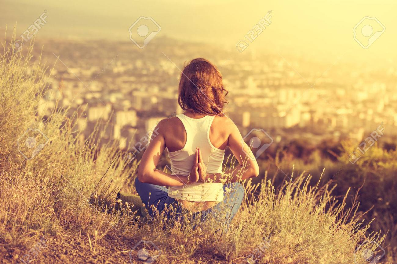 Young woman sits in namaste yoga pose with city on background. Freedom concept. Calmness and relax, woman happiness. Toned image - 43589734