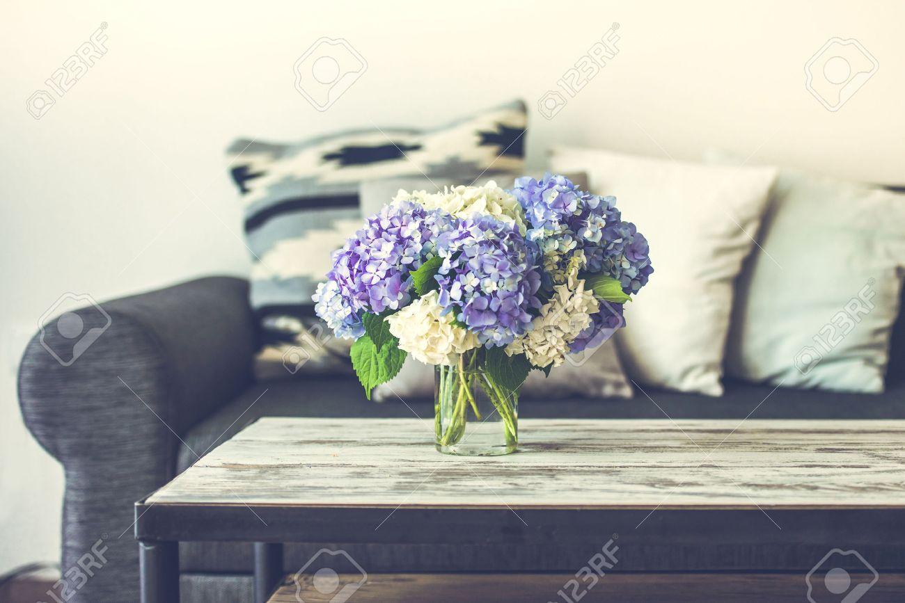 Boeket hortensia bloemen op moderne houten salontafel en gezellige ...