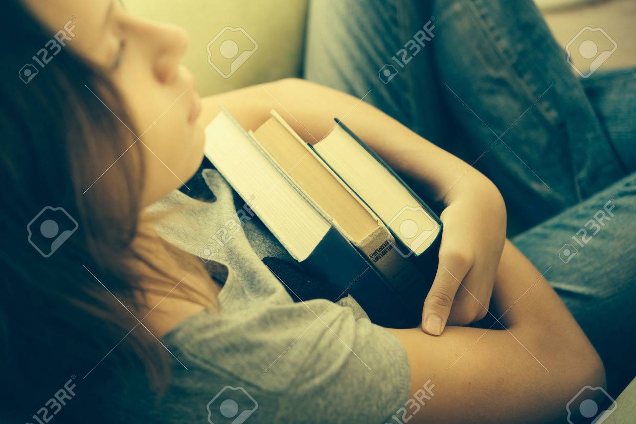 A sad teenage girl sits in armchair holding books. Toned image - 50537337