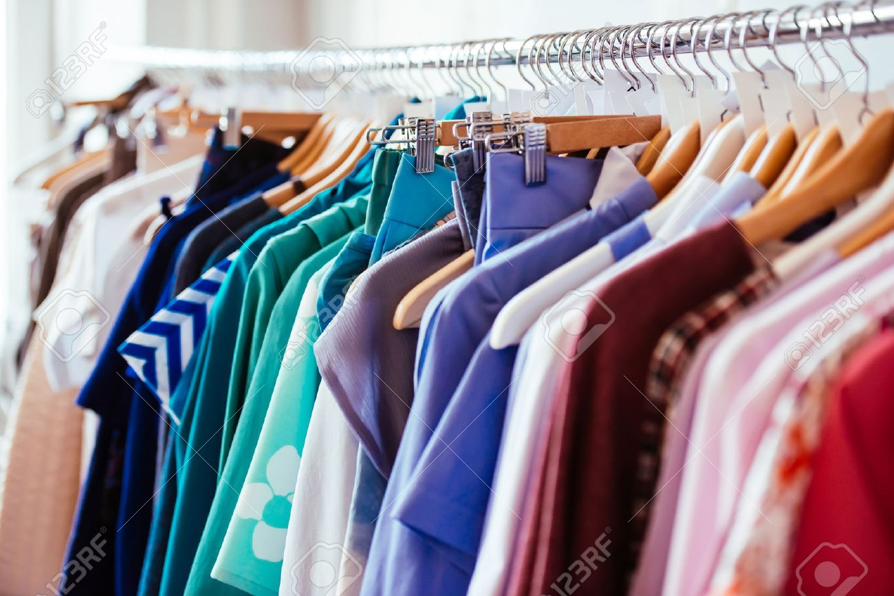 217bbc39ad4c Colorful women s dresses on hangers in a retail shop. Fashion and shopping  concept Stock Photo