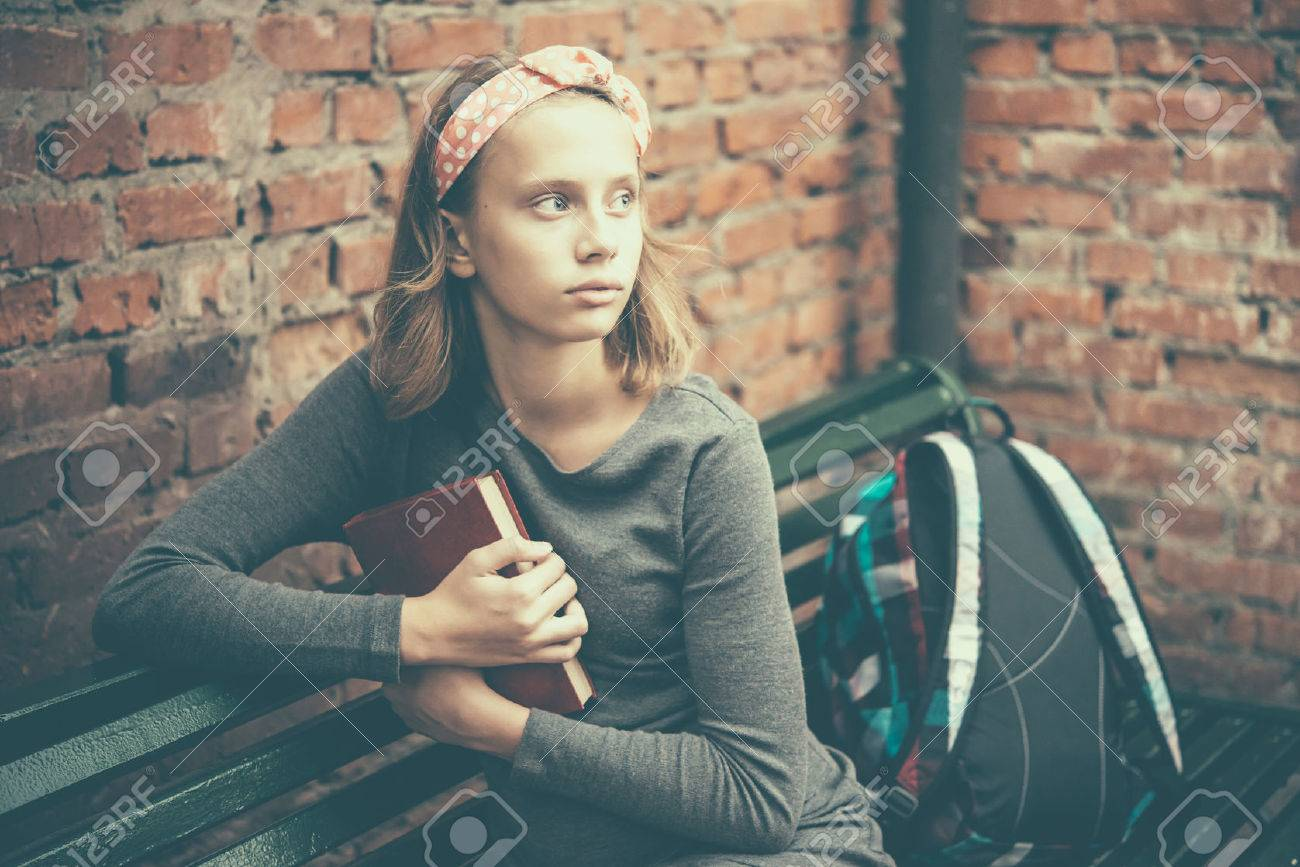 A portrait of a teenage girl sitting on a bench holding a book with brick wall in the background. Toned image - 50614988