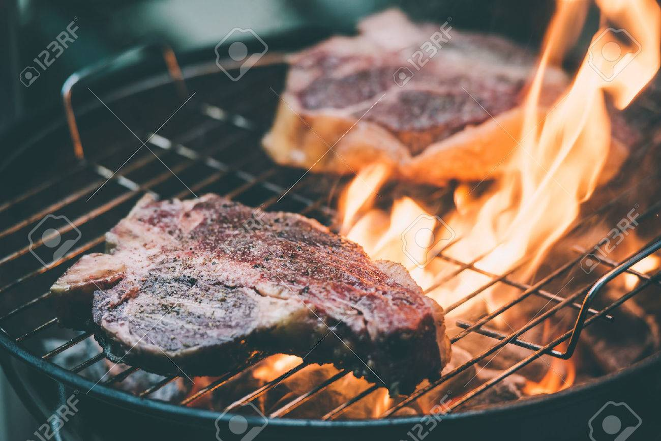 Two t-bone florentine beef steaks on the grill with flames. Toned picture - 50539315