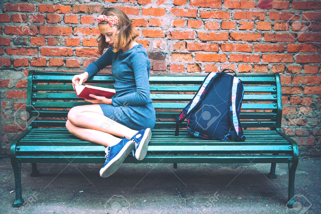 A teenage girl is reading on a bench with brick wall in the background. Toned image - 50840812