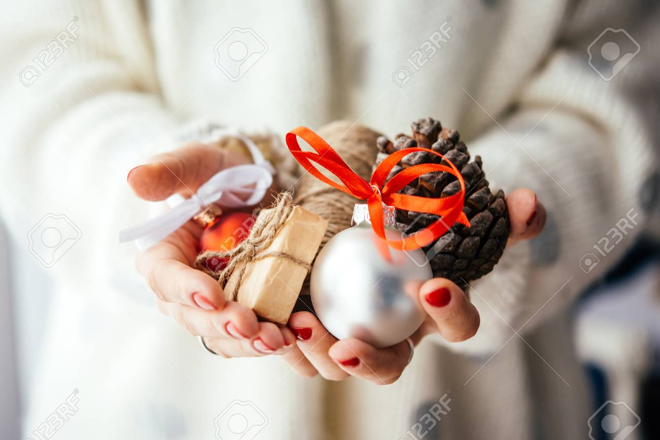 Woman's hands hold christmas or new year decoration. Small gift box, glass ball and cone - 50646068
