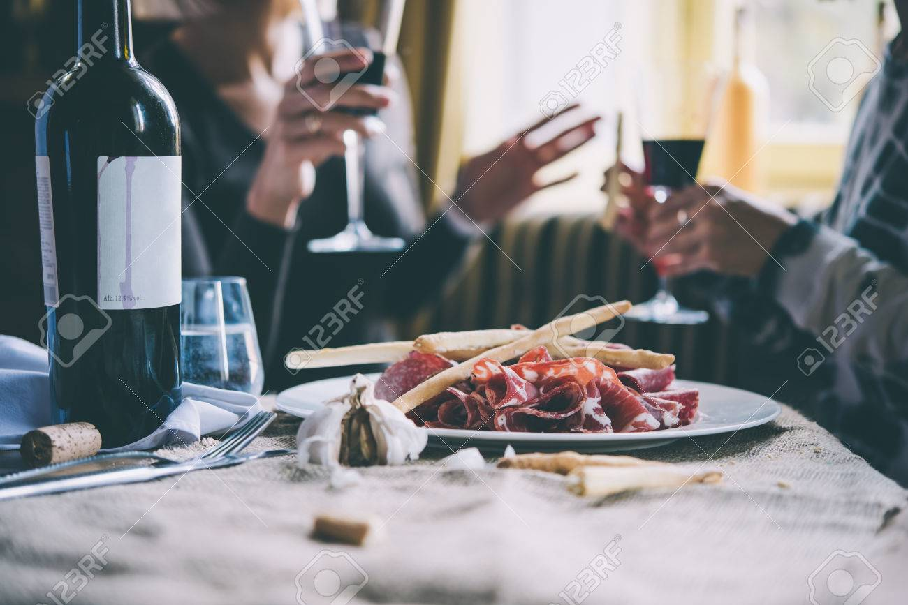 Restaurant or bar table with plate of appetizers and wine. Two people talking on background. Toned picture - 50645753