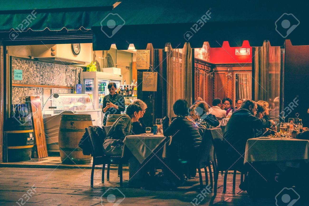 VENICE, ITALY - OCTOBER 11: People are sitting at the outside terrace of a small cafe in the evening in Venice, Italy. Toned picture - 53869822