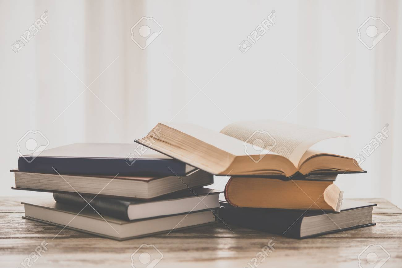 Pile of books on wooden table. Education and reading concept. Toned picture - 55411687