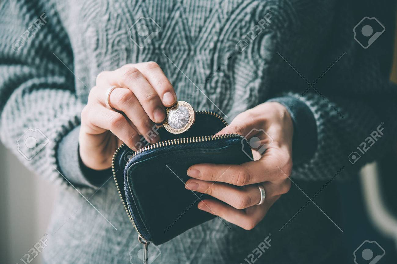 Hands holding british pound coin and small money pouch. Toned picture - 55411679