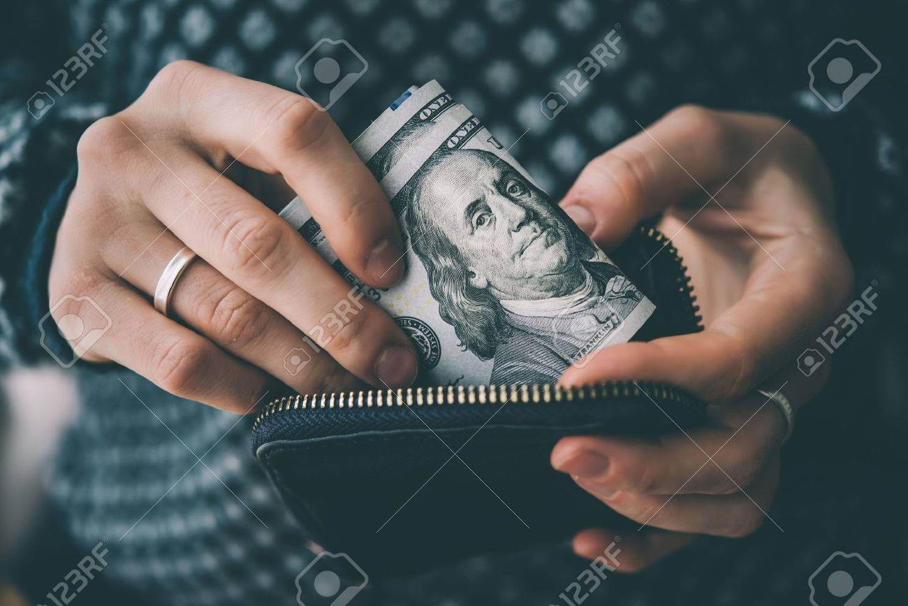 Hands holding us dollar bills and small money pouch. Toned picture - 55416821