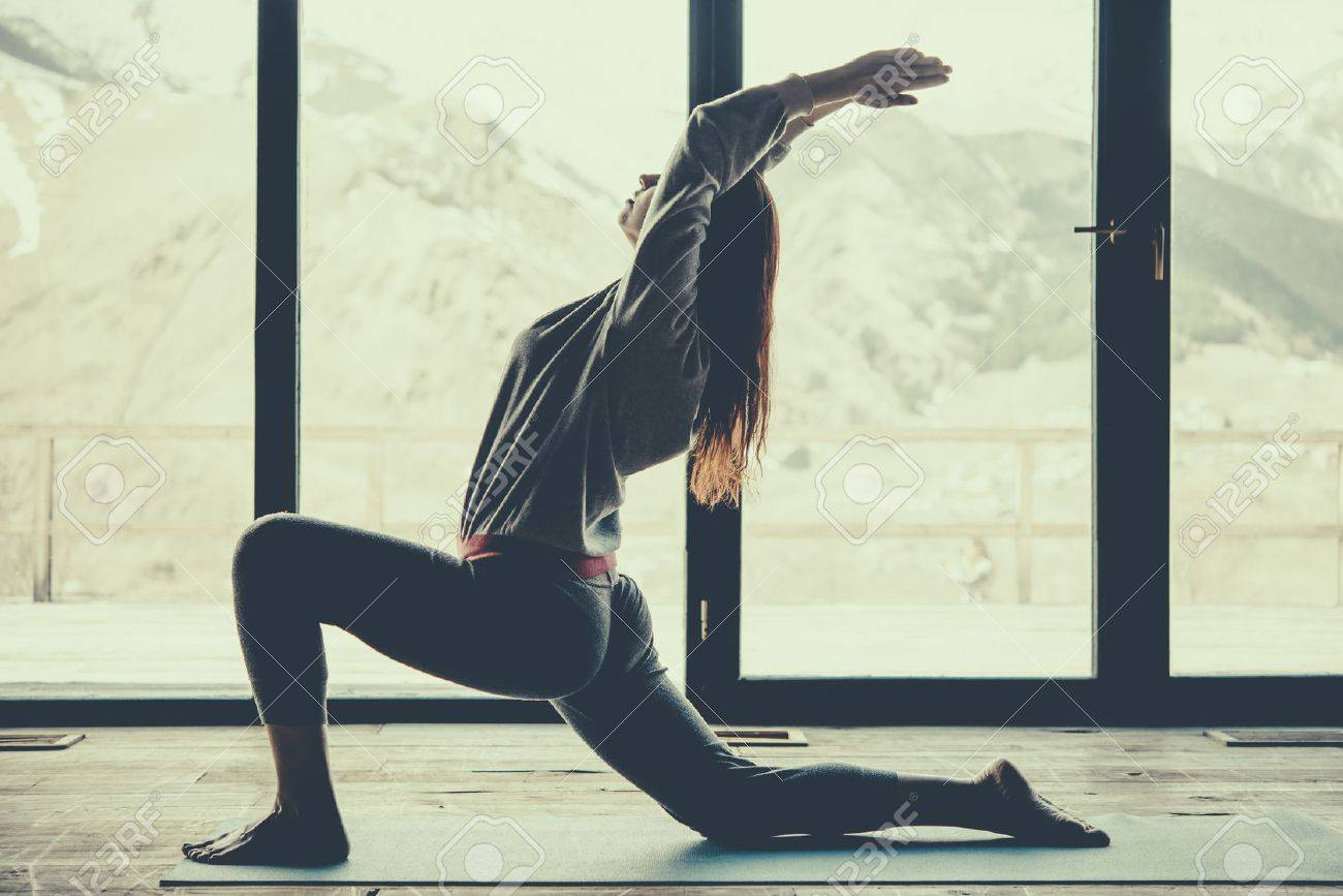 Young beautiful woman practicing yoga with mountain view in the background. Freedom concept. Calmness and relax, woman happiness. Toned picture - 58510659
