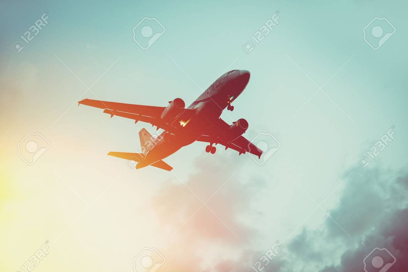 Passenger plane in the sky at sunrise or sunset. Vacation and travel concept. Toned image - 58622595
