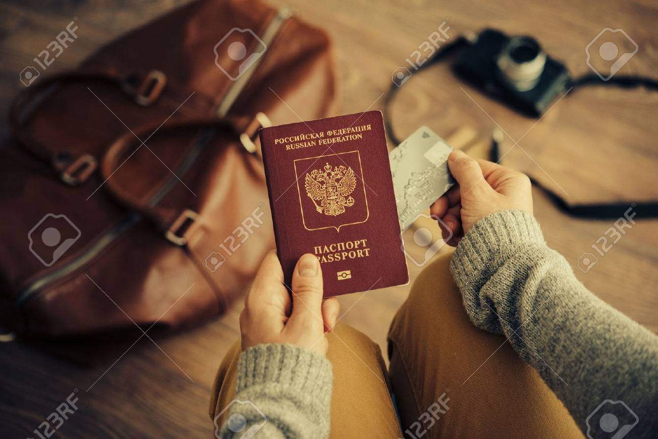 Person holds Russian travel passport and plastic credit card in hands with leather bag and photo camera in the background. Travel and tourism concept. Toned picture - 60578229