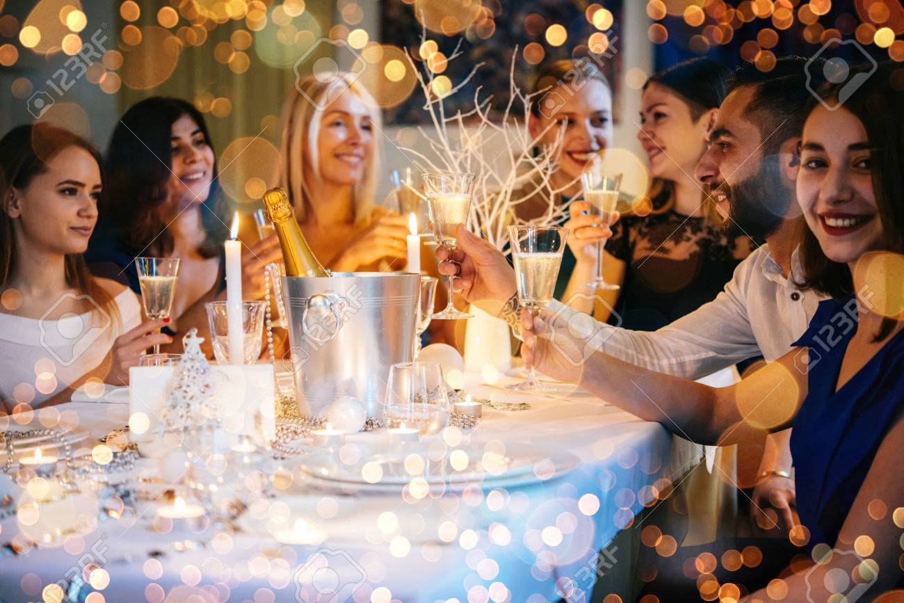 Friends celebrating Christmas or New Year eve. Party table with champagne. - 69759412