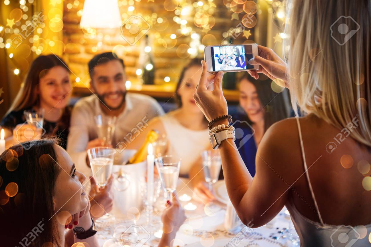 Friends celebrating Christmas or New Year eve. Party table with champagne. - 69759388