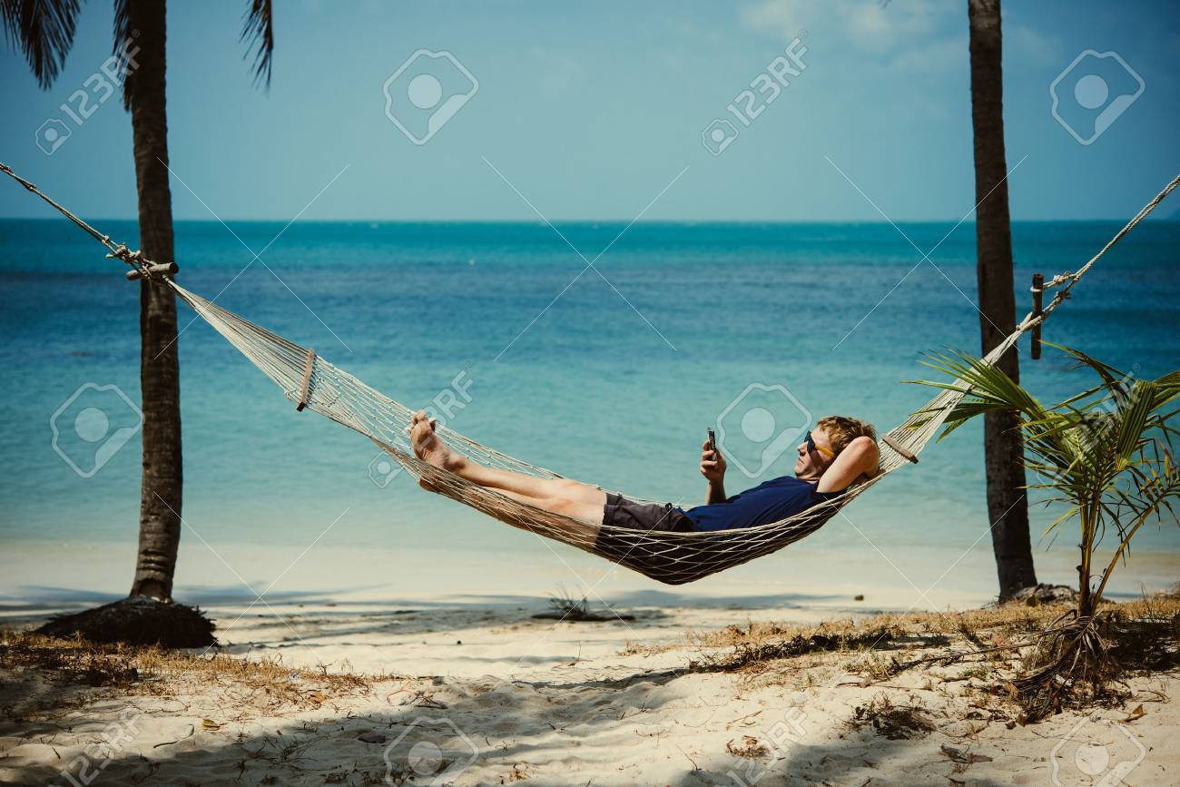A young man relaxes in a hammock at the beach while checking messages on his smartphone. Toned image - 69677423
