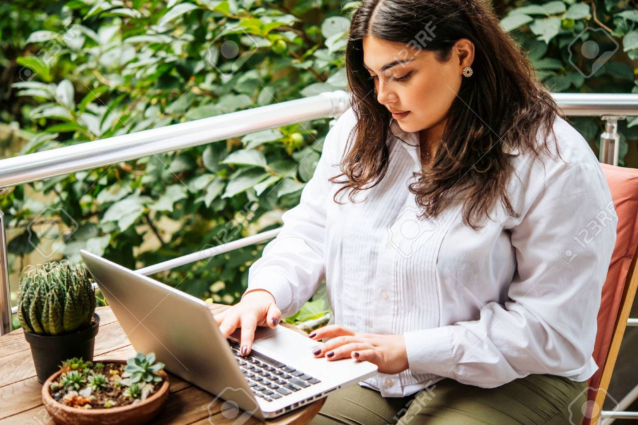 Portrait of beautiful plus size girl working on her laptop on balcony or terrace of cafe - 73658075
