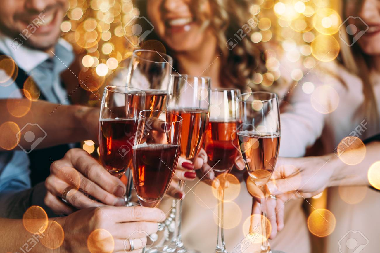 Friends celebrating Christmas or New Year eve with glasses of rose champagne - 89627388