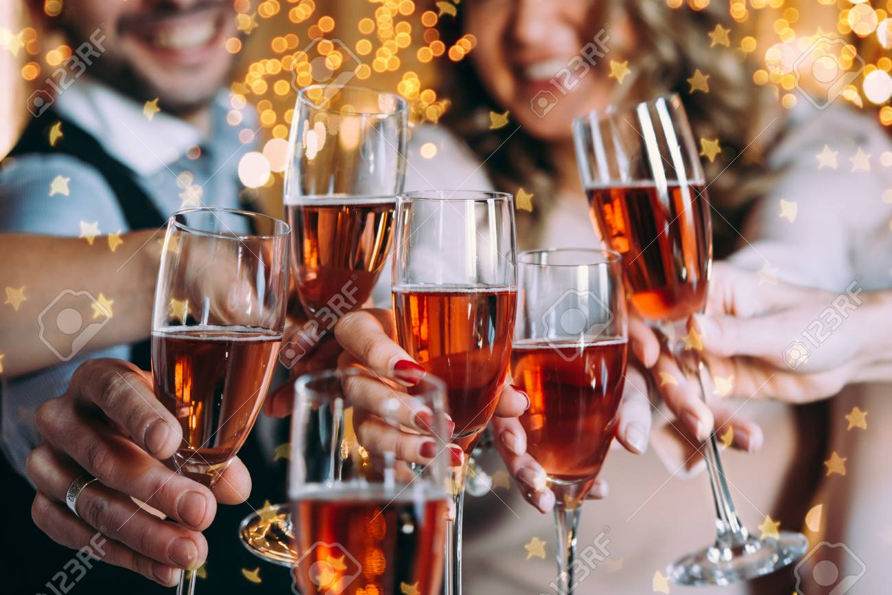 Friends celebrating Christmas or New Year eve with glasses of rose champagne - 90280766
