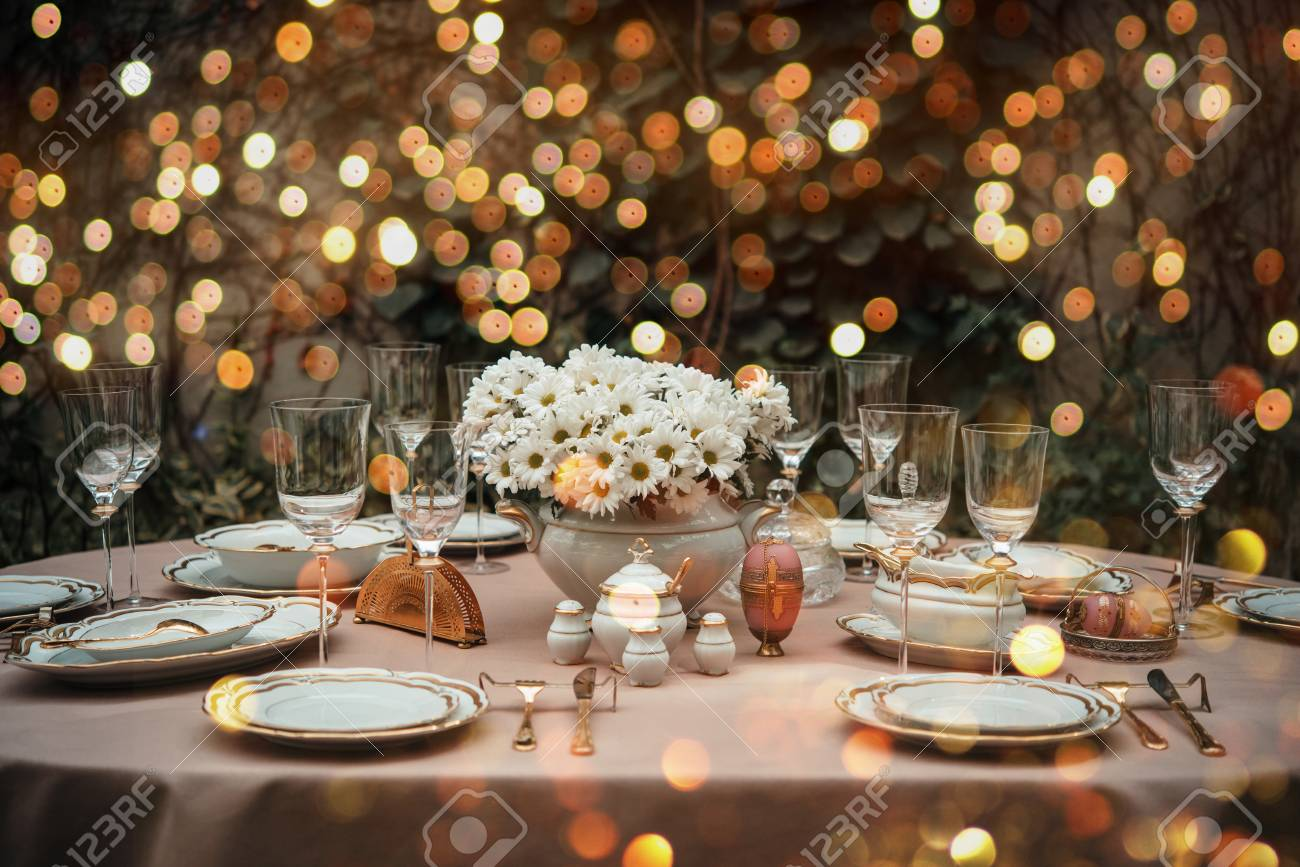Table served for luxury dinner party lighted with garlands - 102187785