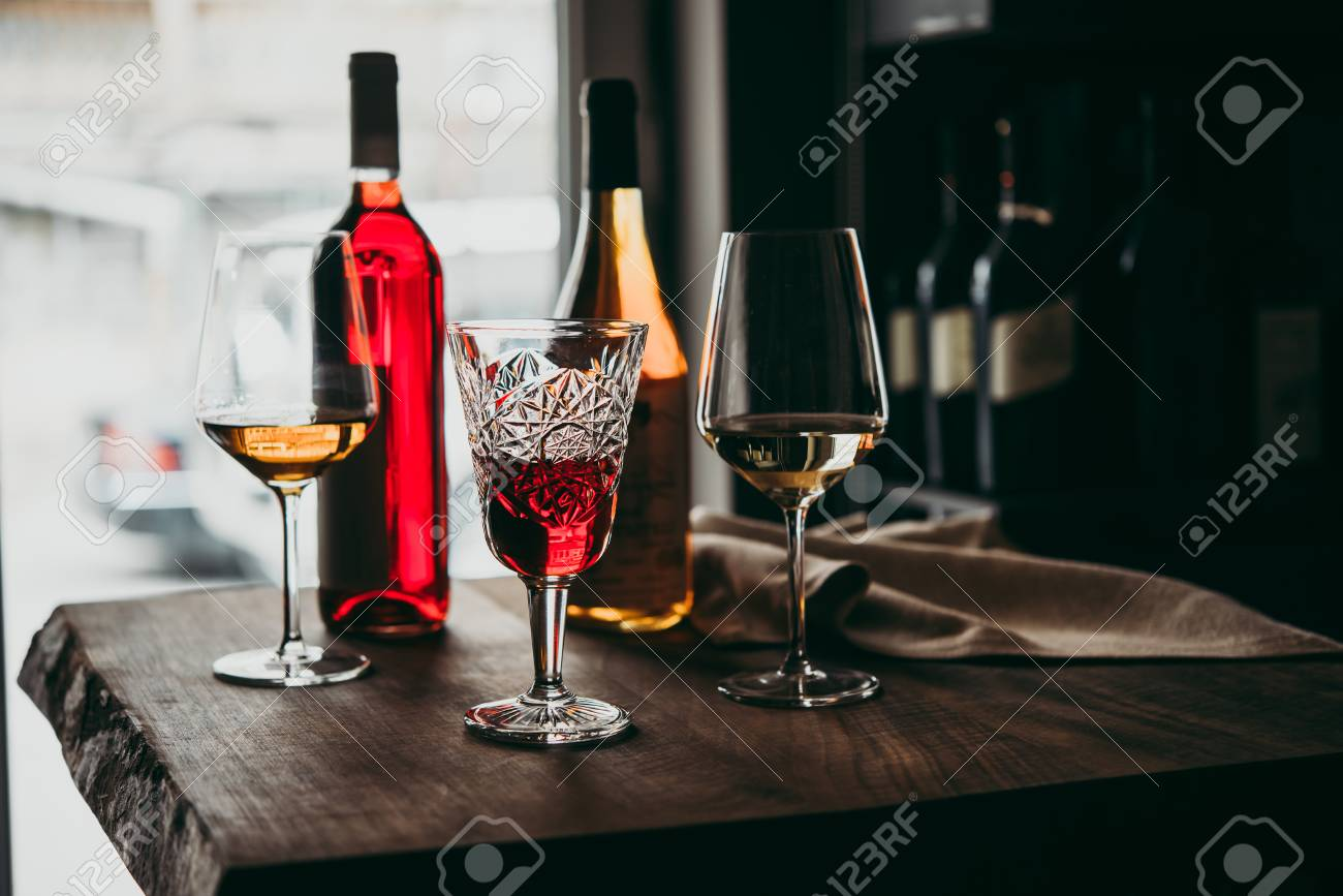 Different glasses and bottles of wine served on a wooden table in a bar or a wine shop. - 103759200