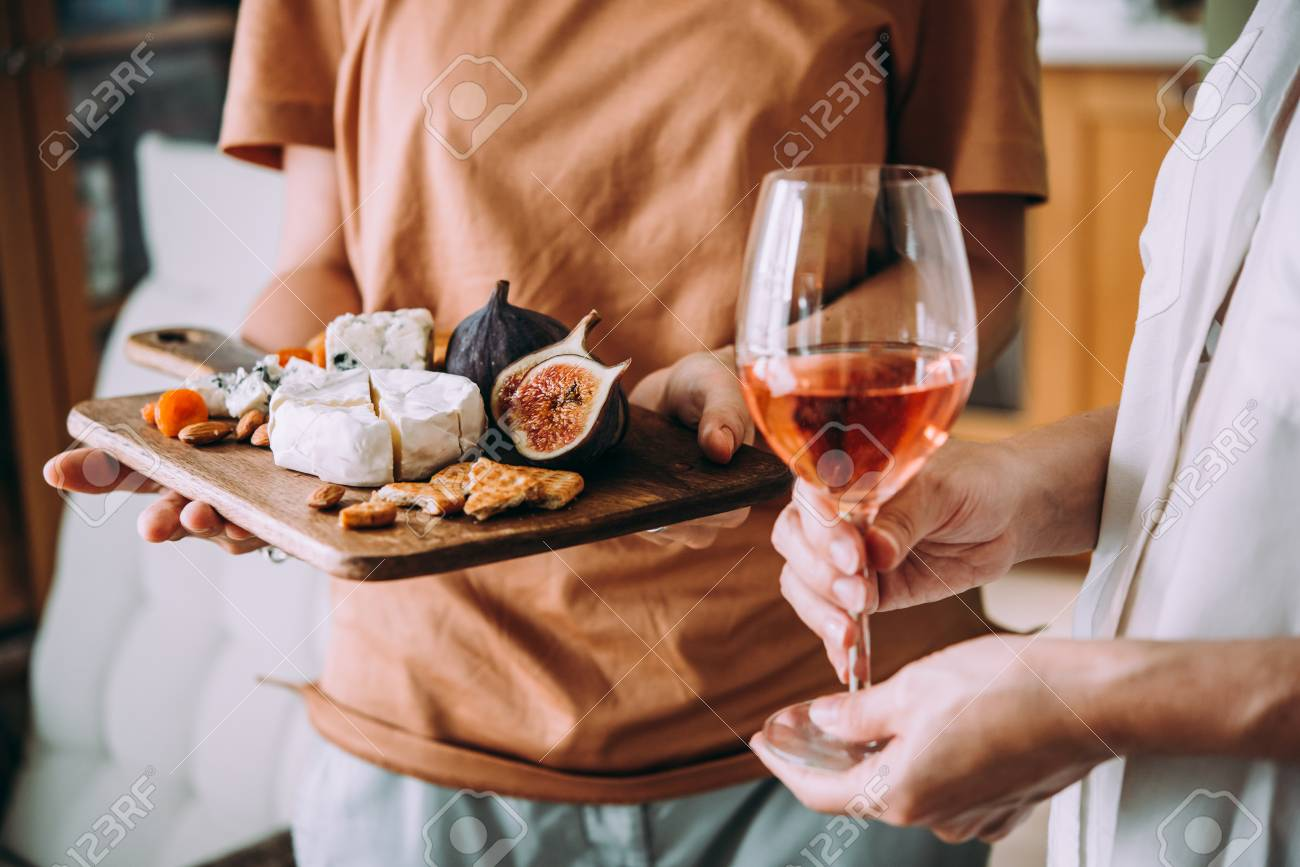 Hands holding a glass of wine and a wooden board with different kinds of cheese and dried fruits. Dinner or aperitivo party concept. - 109931583