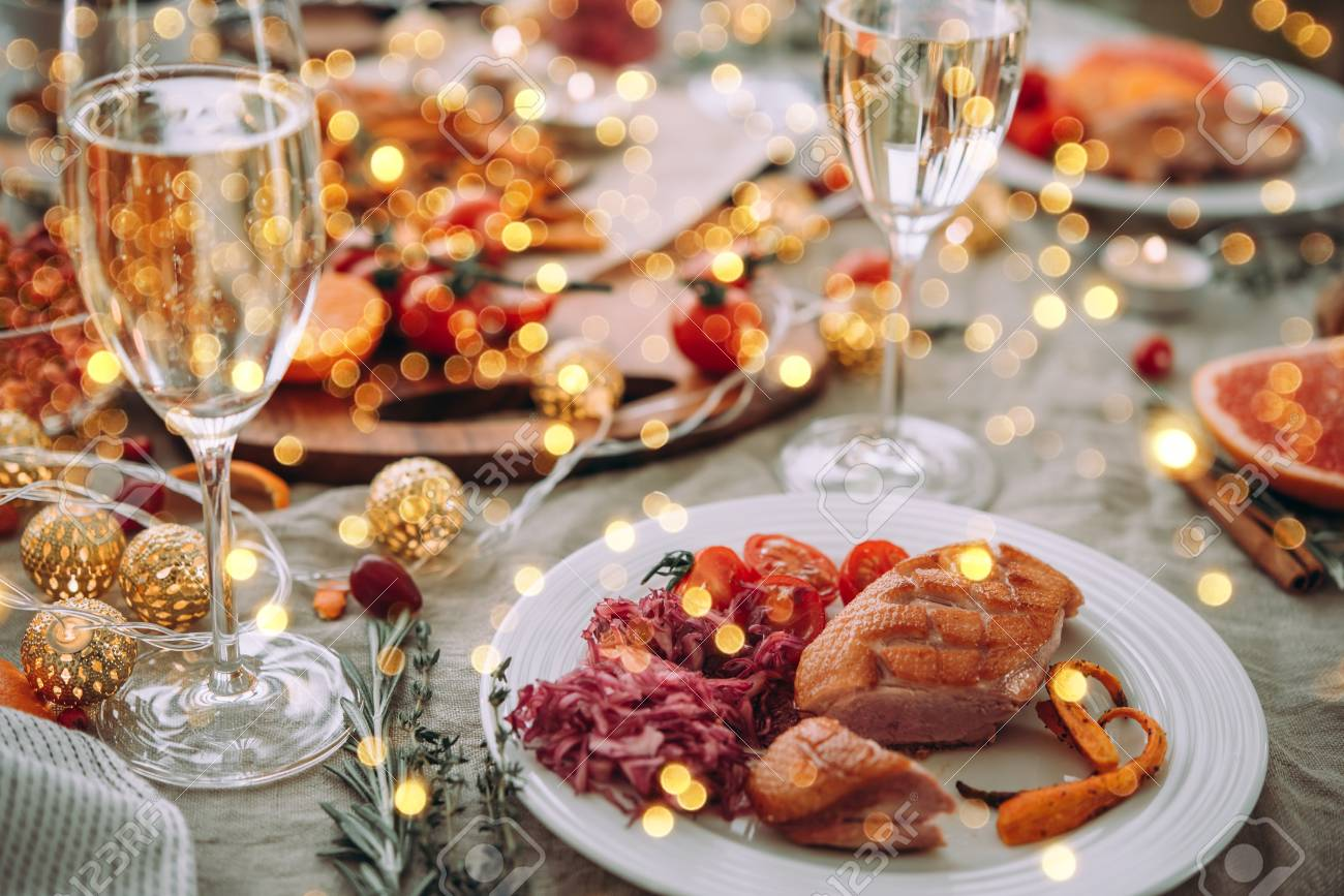Roasted duck or turkey. Party table with glasses of champagne. Friends celebrating Christmas or New Year eve. - 110131905