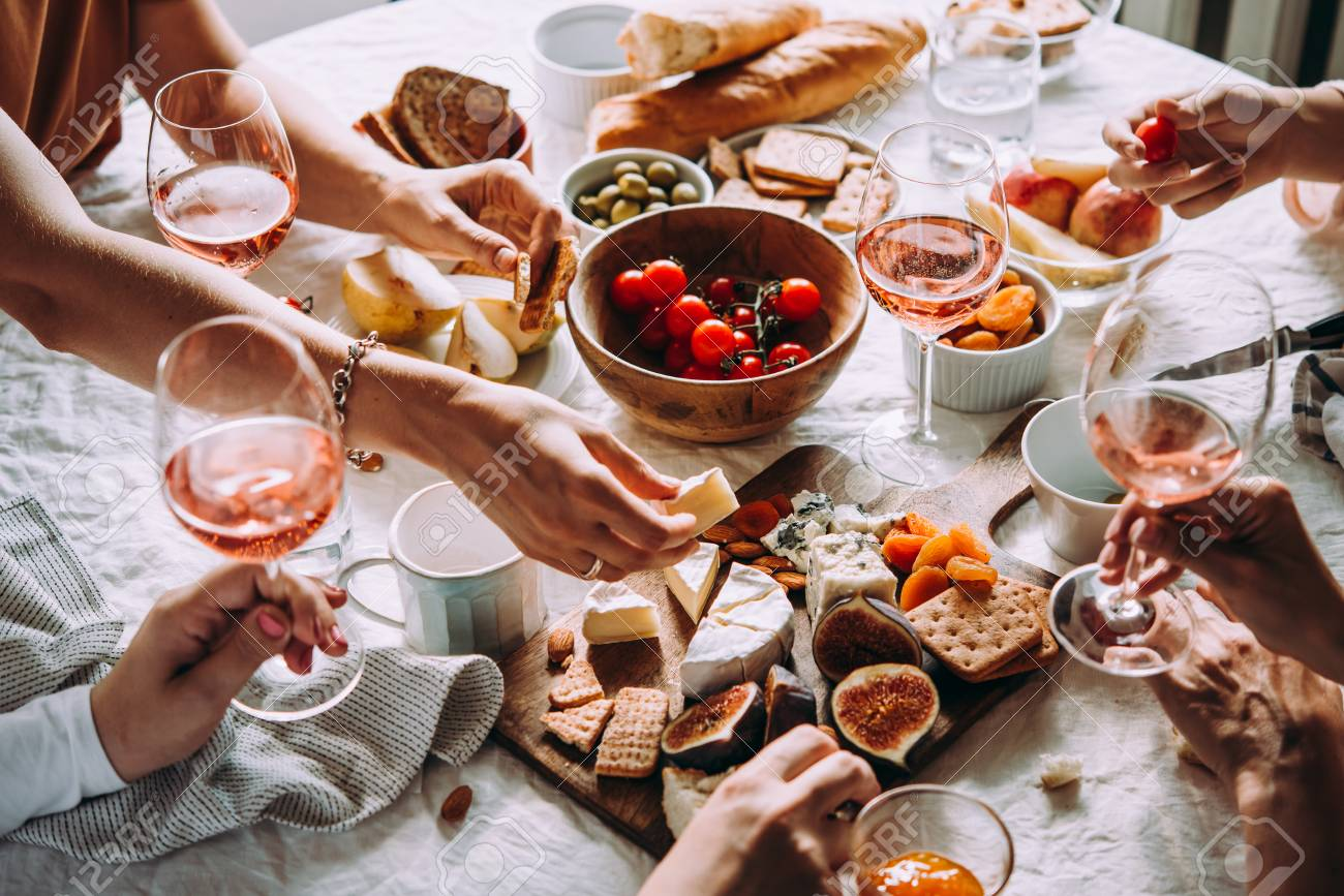 Friends having a dinner party with different kinds of appetizers and rose wine. - 110132262