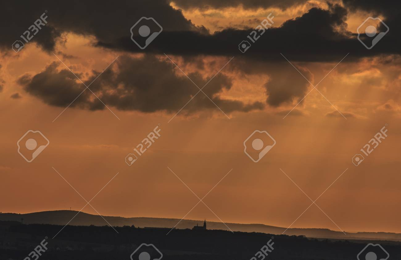 Small Silhouette Of A Country Church Backgrounded Against Orange Sky At Sunset Stock Photo