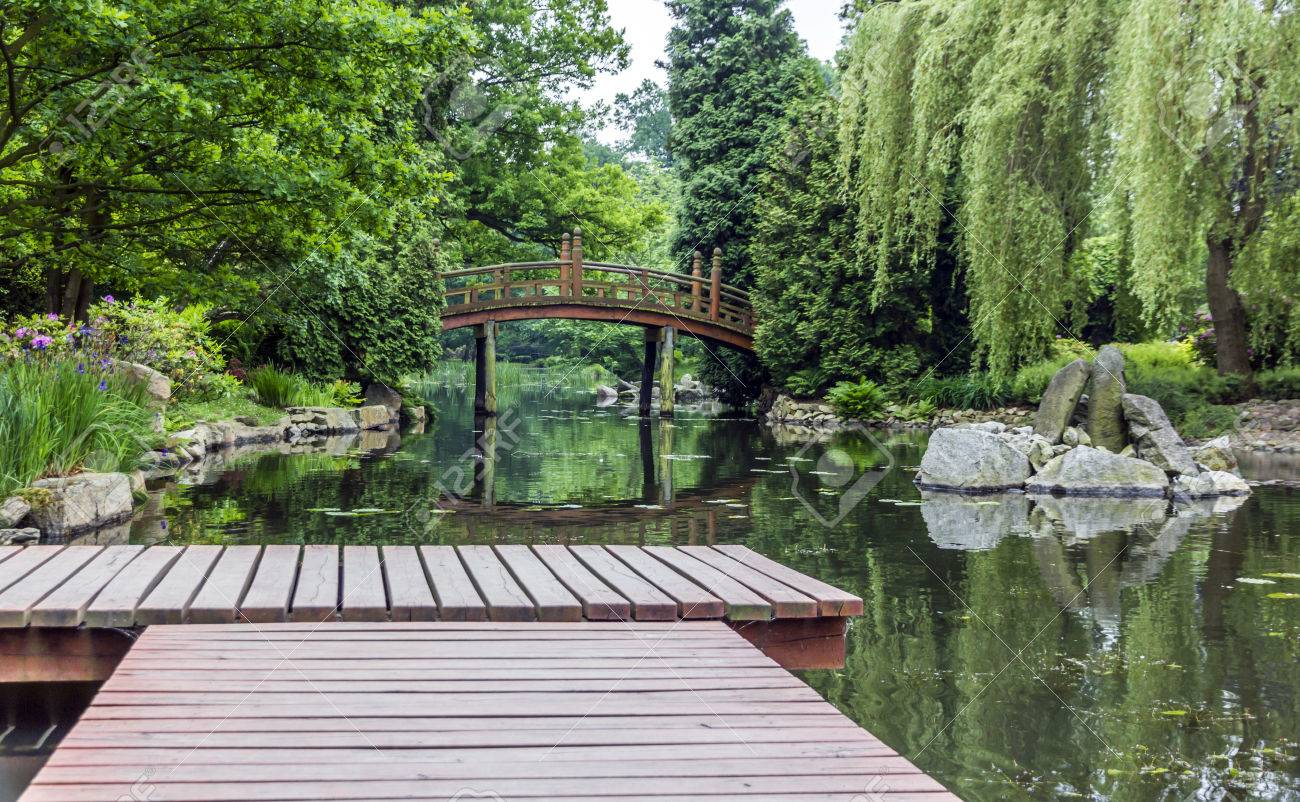 pier in japanese garden with red japanese bridge in background stock photo 29266939