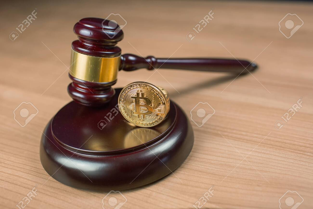 Bitcoin regulation. BTC cryptocurrency coin and judge gavel on a desk. Banned currency or law enforcement concept. - 123389986
