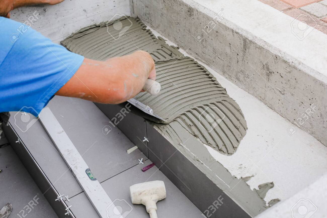 Tiler hands working on a new house entrance, local and professional handyman applying tiles to the steps. - 129975050